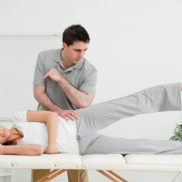 Doctor pressing his elbow on her hip while woman raising her leg in a room